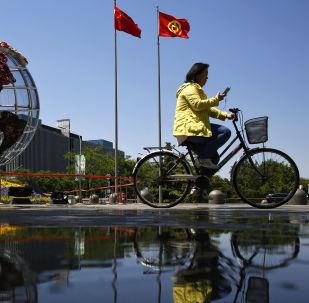 Žena jede na kole před budovou banky v Pekingu