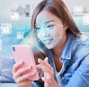 Dívka s chytrým telefonem se systémem rozpoznávání tváří