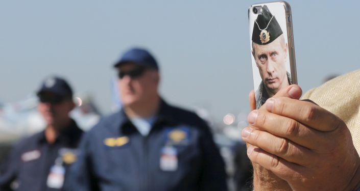Návštěvník MAKS 2015 fotografuje telefonem s obrazem ruského prezidenta Vladimira Putina.