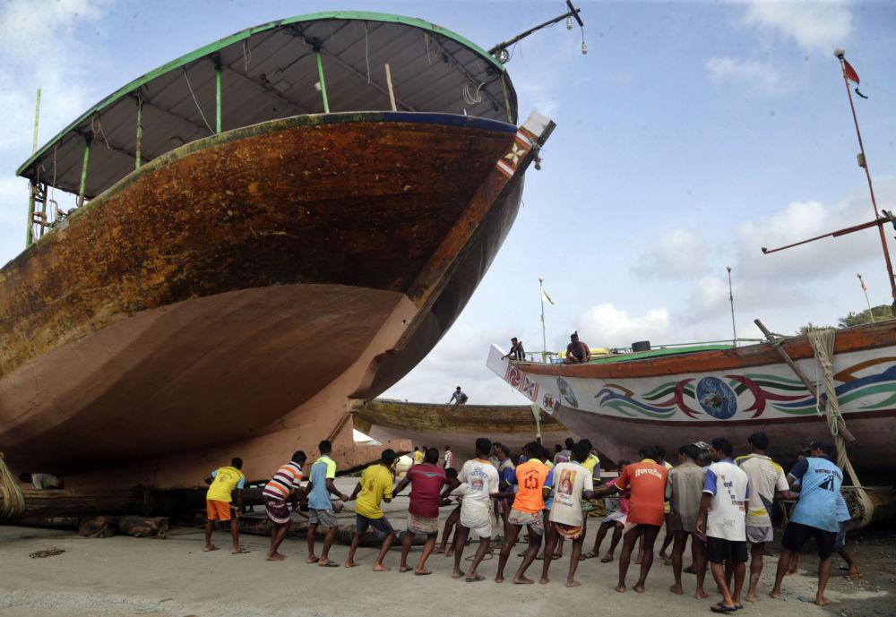 Indičtí rybáři přepravují loď na suchou půdu před začátkem monzunového období dešťů.