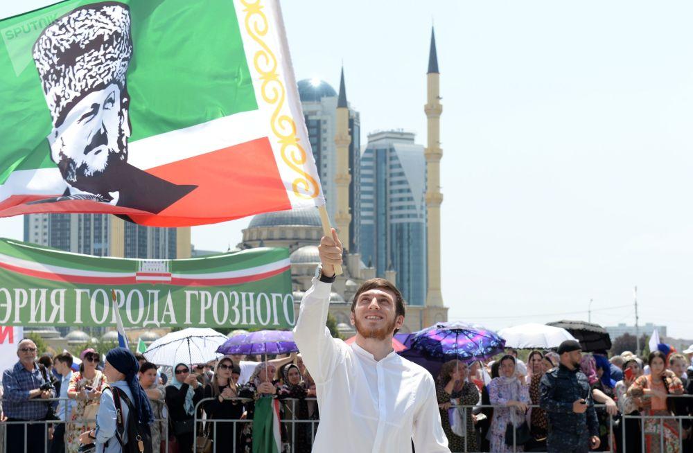 Oslavují i v čečenském Grozném. Muž mává čečenskou vlajkou s portrétem prvního čečenského prezidenta Achmatem Kadyrovem.