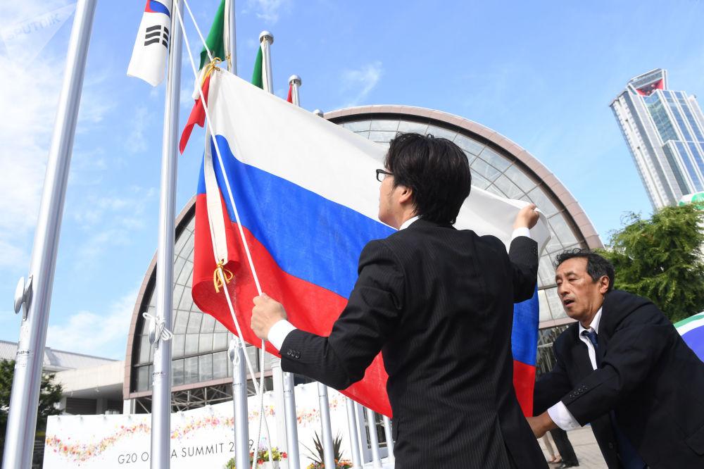 Organizátoři vztyčují ruskou vlajku před výstavištěm INTEX v Ósace, kde se konal summit G20.