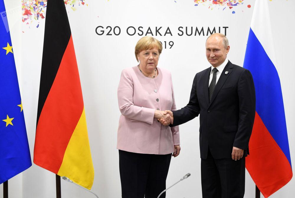 Prezident Ruska Vladimir Putin a německá kancléřka Angela Merkelová si podávají ruce na okraji summitu G20 v Ósace.