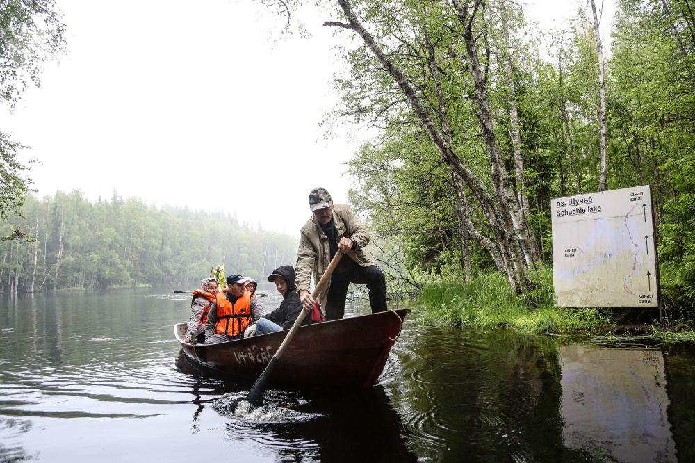 Turisté plují na lodi podél umělých kanálů mezi jezery na Soloveckých ostrovech