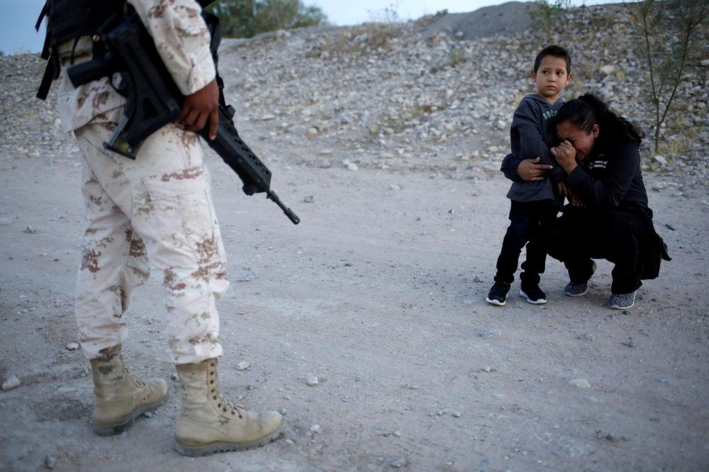 Migrantka z Guatemaly Lety Perezová se svým synem Anthonym prosí příslušníka mexické národní gardy, aby je nechal překročit hranice a dostat se do USA.