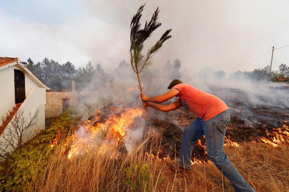Místní hasí požar ve vesnici Kolos, Portugalsko.