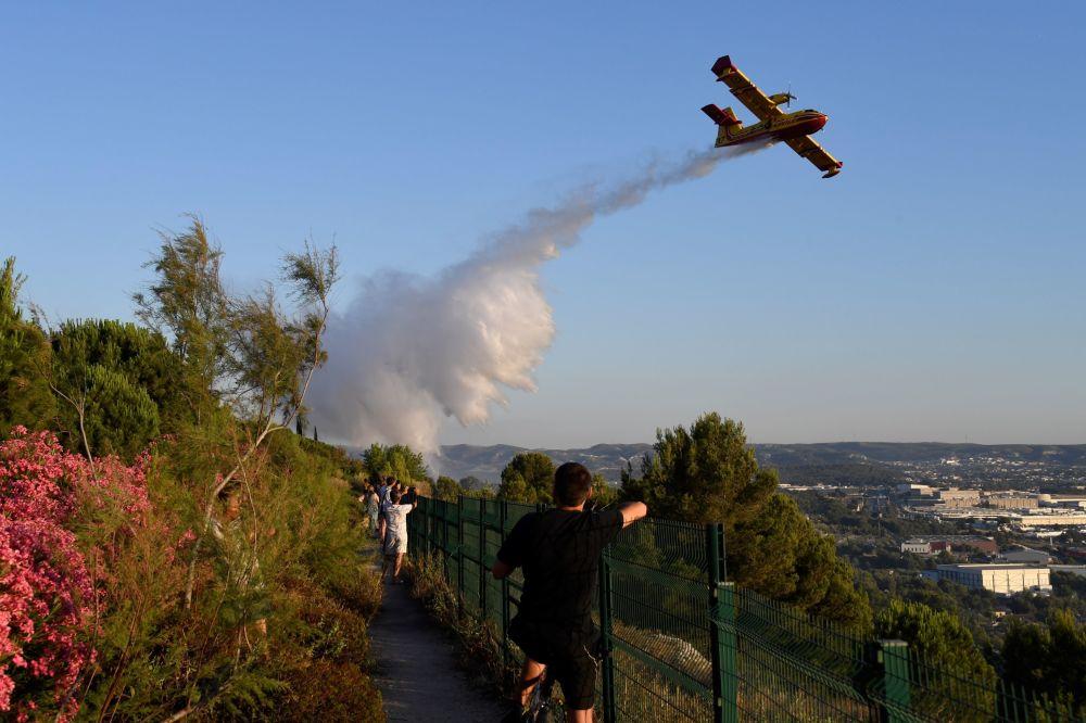 Hasičské letadlo Canadair svrhává vodu nad ohněm, které se rozhořelo v průmyslové zoně Vitrol v jihovýchodní Francii.