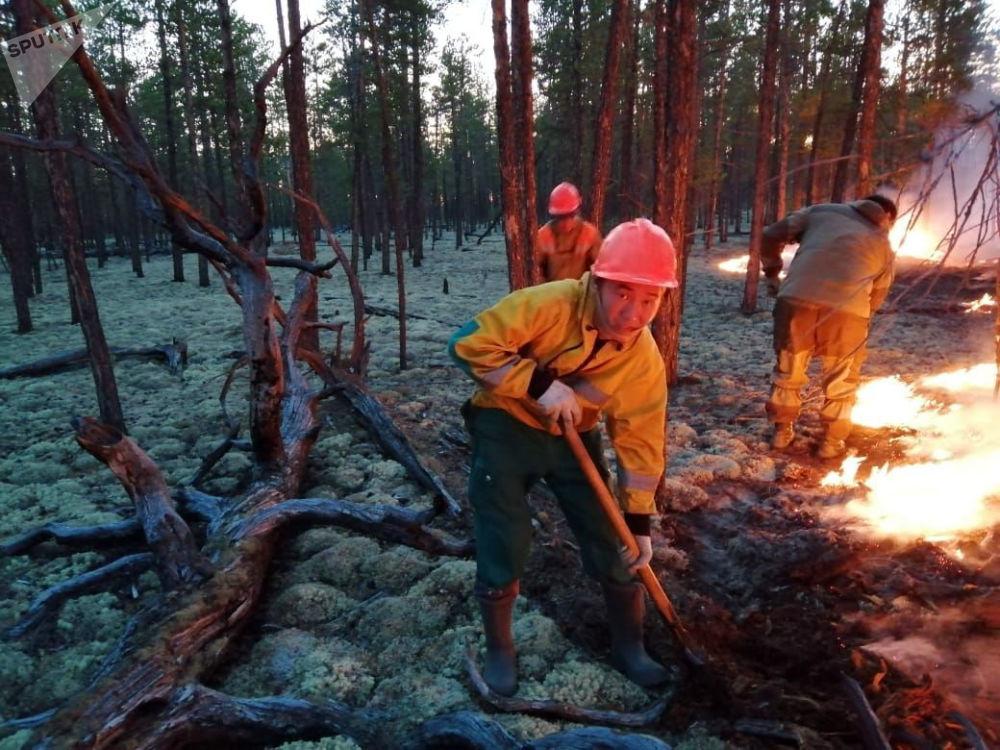 Pracovníci Ministerstva ochrany přírody Jakutsku hasí hořící les.