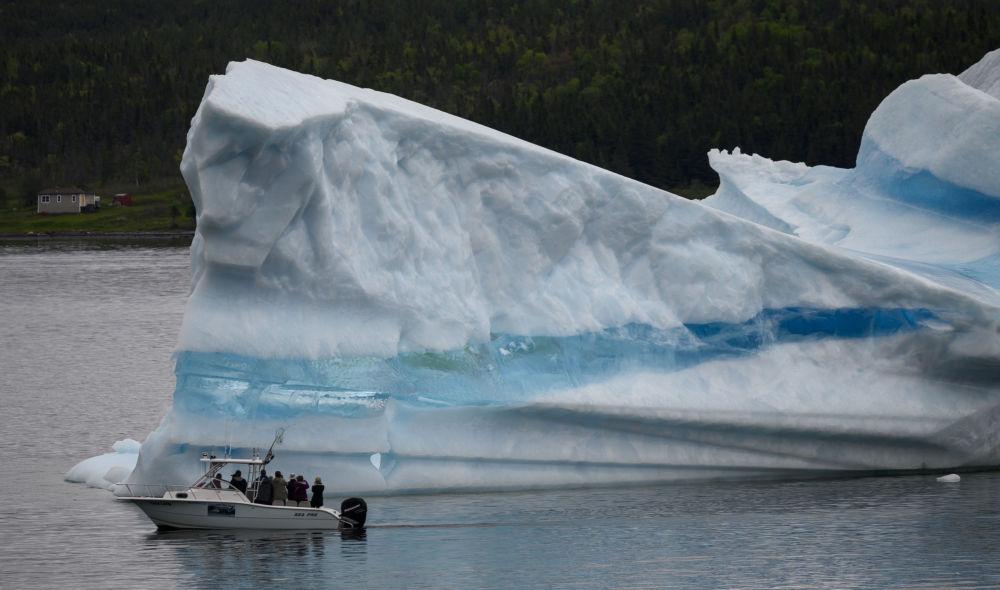 Turisté sledují z lodi ledovce poblíž Kings Point, Newfoundland, Kanada