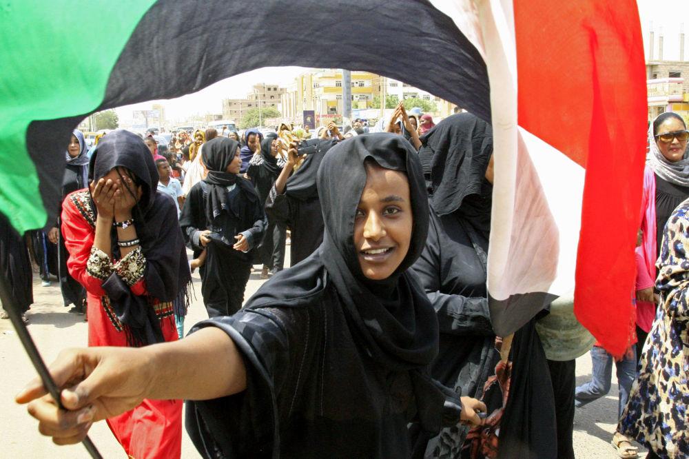 Súdánská dívka s národní vlajkou při oslavě podpisu Ústavní dohody o zřízení dočasné vlády mezi vojenskou radou a frontou národního osvobození.