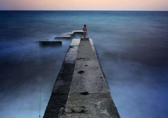 Dívka na vlnolamu v Aluště, Krym.