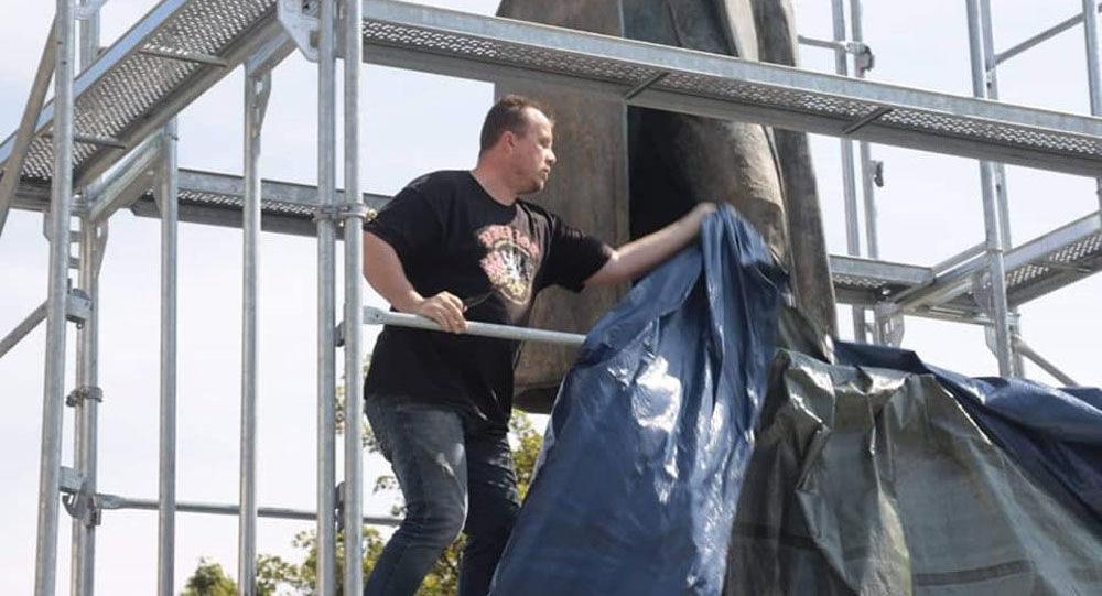 Aktivista strhává plachty ze sochy maršála Koněva