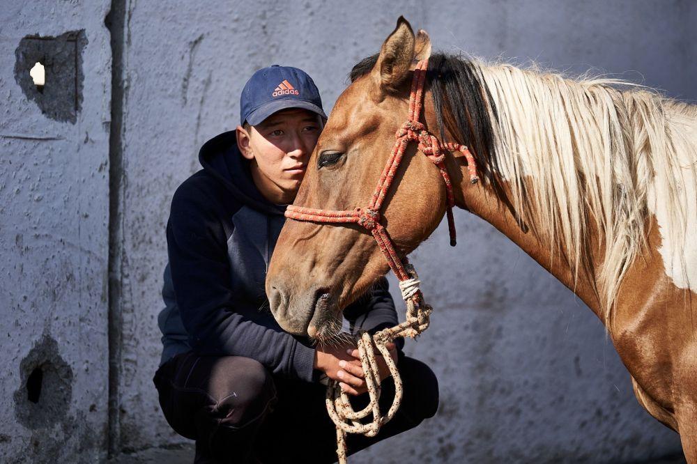 Mladý muž prodává koně na největším trhu zvířat v Kyrgyzstánu