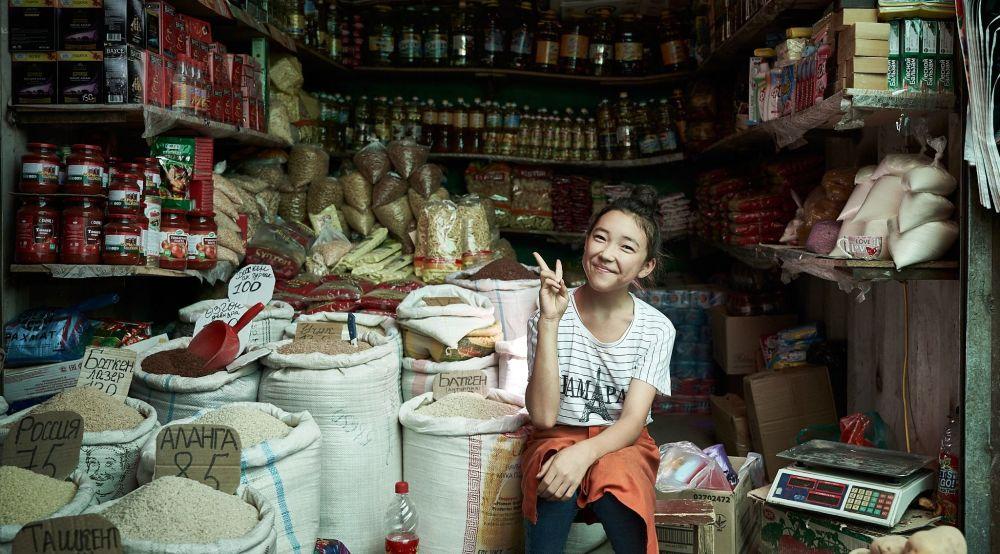 Mladá prodavačka prodává potraviny na hlavním trhu ve městě Oš v Kyrgyzstánu