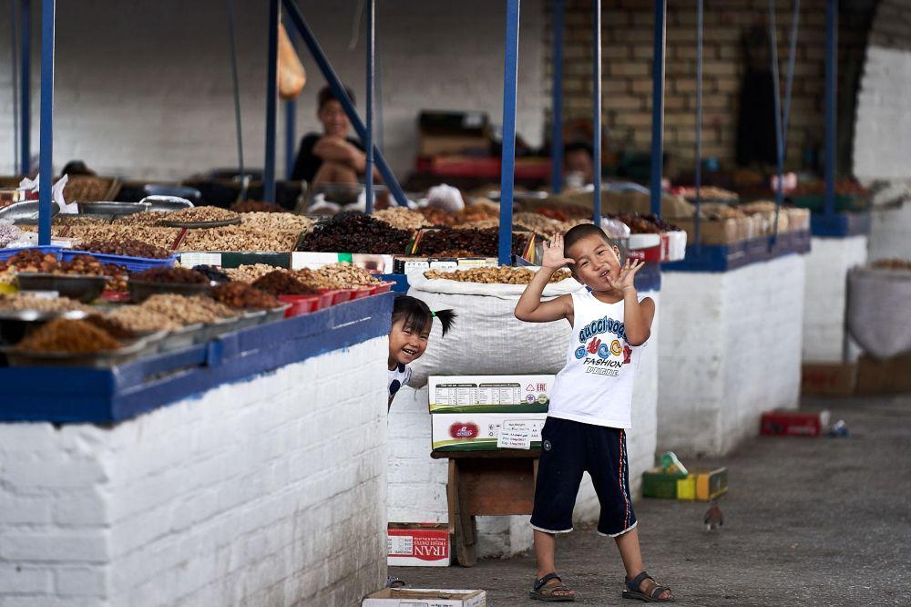 Smějící se děti na trhu v Kyrgyzstánu