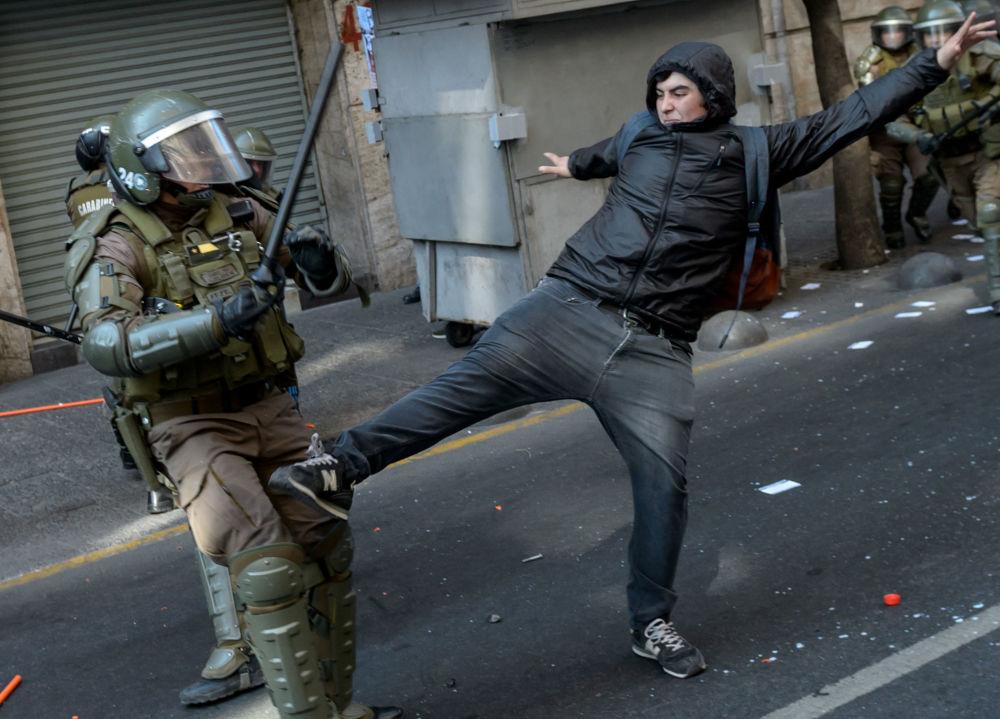 Střety mezi protestujícími a policií během akce u příležitosti 46. výročí vojenského převratu vedeného generálem Augustem Pinochetem v Chile.
