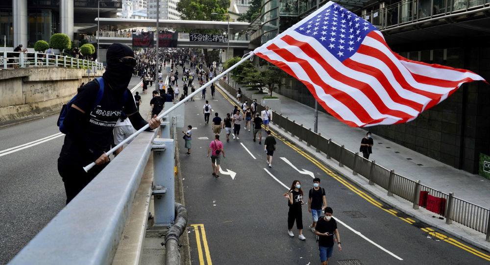 Demonstrant v Hongkongu mává americkou vlajkou