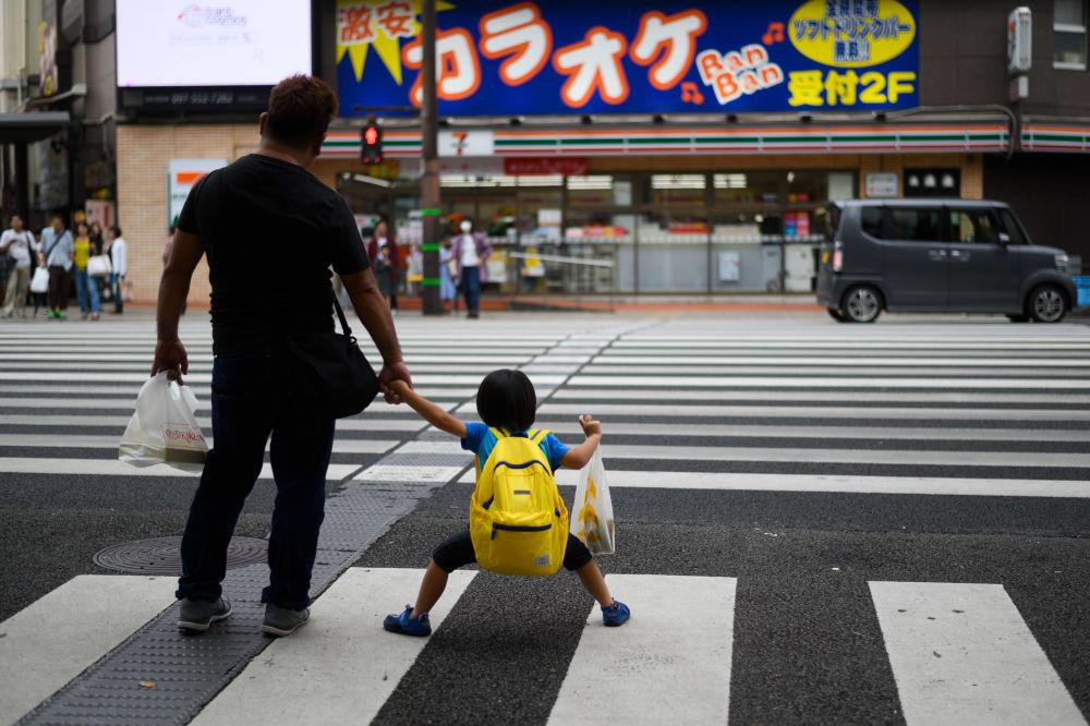 Muž se synem na přechod pro chodce v centru Oita