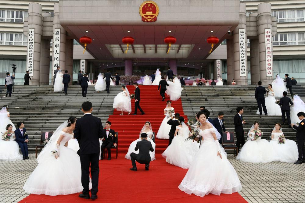 Novomanželé na hromadné svatbě v budově městské vlády v předvečer 70. výročí ČLR