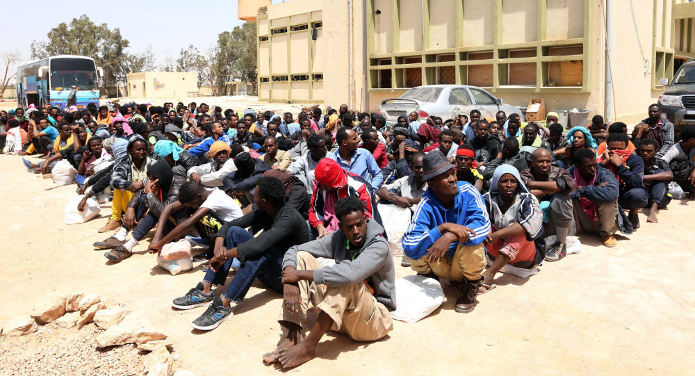 Migranti z Afriky sedí v blízkosti centra pro nelegální migranty v Misuratu