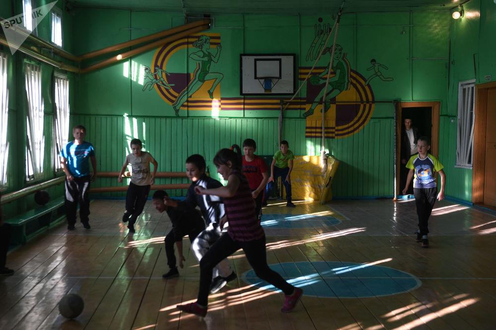 Děti hrají fotbal ve školní tělocvičně