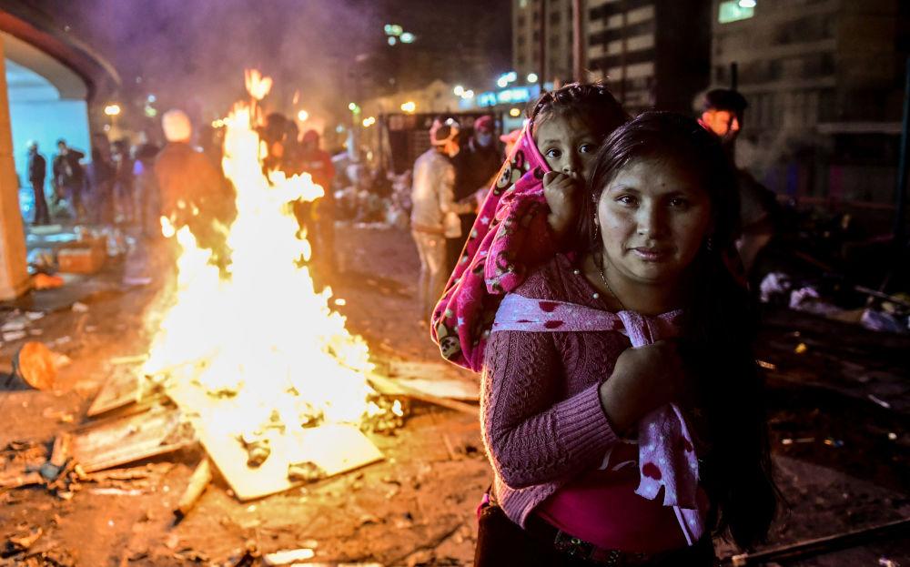 Žena s dcerou během protestů v ekvádorském Quito.