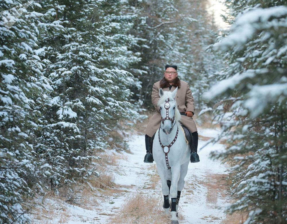 Lídr KLDR Kim Čong-un jede na koni v prvním sněhu na hoře Pektusan.