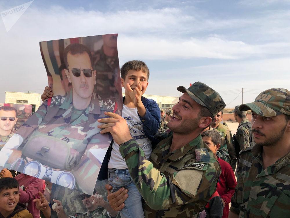 Děti a vojáci s plakáty se syrským prezidentem Bašárem Asadem ve městě Manbidž, které bylo osvobozeno syrskou vládní armádou.