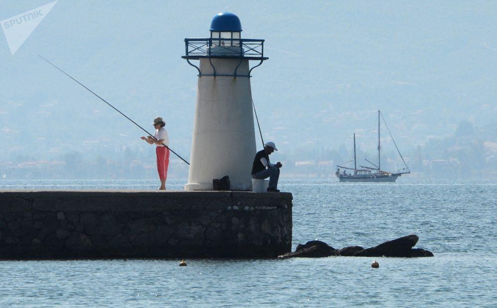 Rekreanti rybaří na pobřeží Egejského moře.