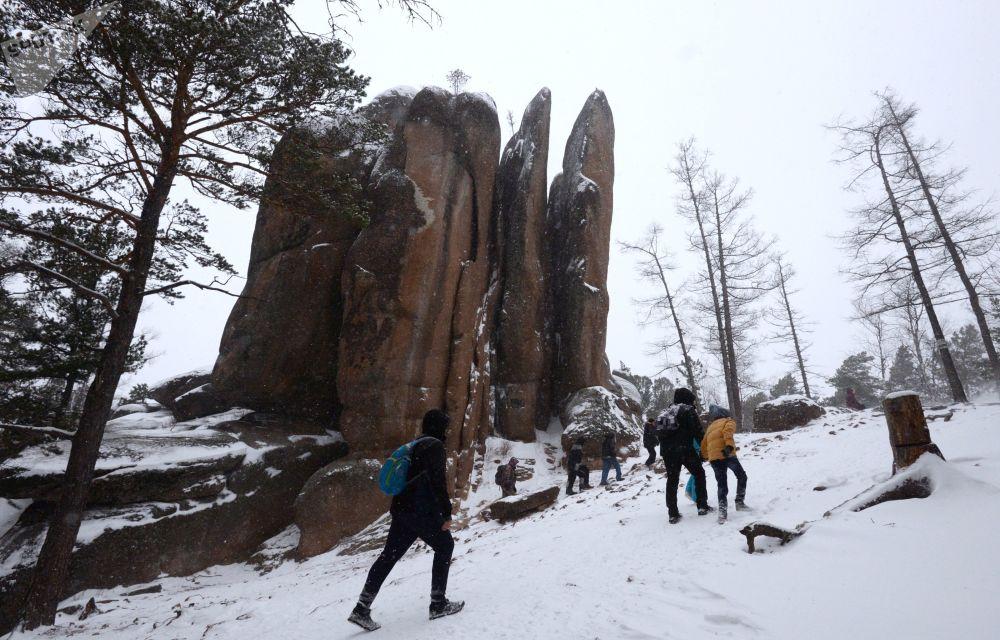 Turisté na úpatí syenitové skály Peří v Krasnojarském kraji.