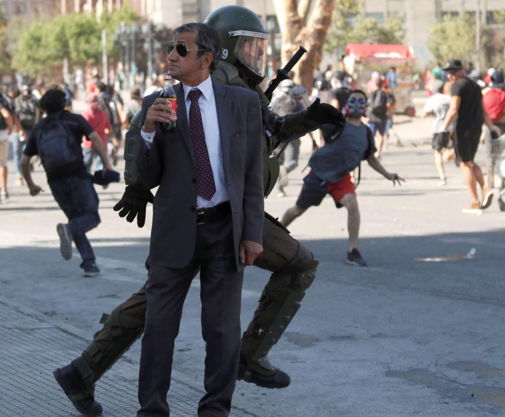 Muž s lahví Coca-Coly během protivládní demonstrace v Santiagu v Chile.