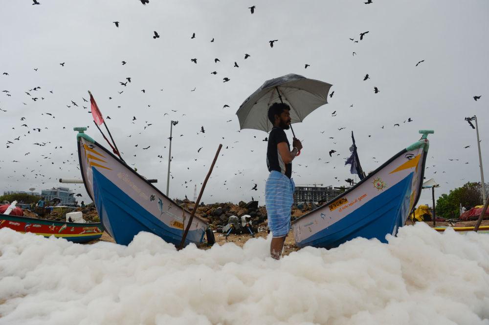 Můž na pláži s toxickou pěnou v Indii.