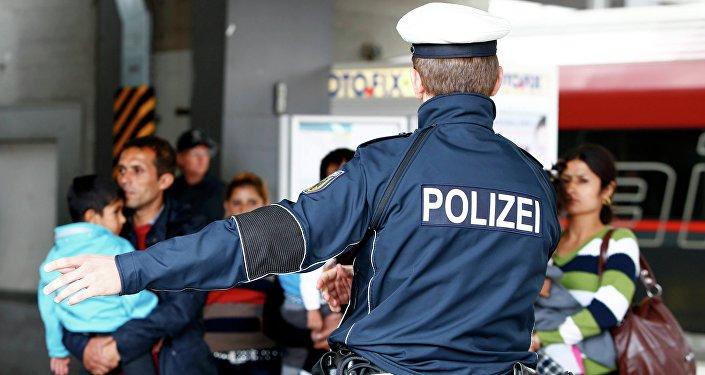 Německý policista a migranti. Ilustrační foto