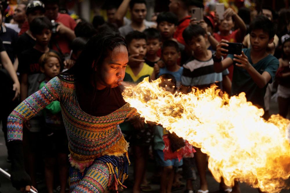 Pouliční umělec vyfouká oheň z úst na oslavě čínského Nového roku v Manile na Filipínách