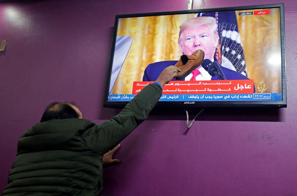Palestinec položil botu na televizní obrazovku v kavárně v Hebronu, na níž Donald Trump hovoří o svém plánu na blízkovýchodní urovnání
