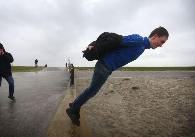 Muž na pobřežní hrázi během bouře Sabine v Nizozemsku