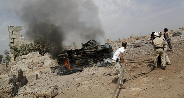Členové civilní obrany uhasili plameny na hořícím vojenském vozidle v jižním Idlibu, Sýrie 1. října 2015