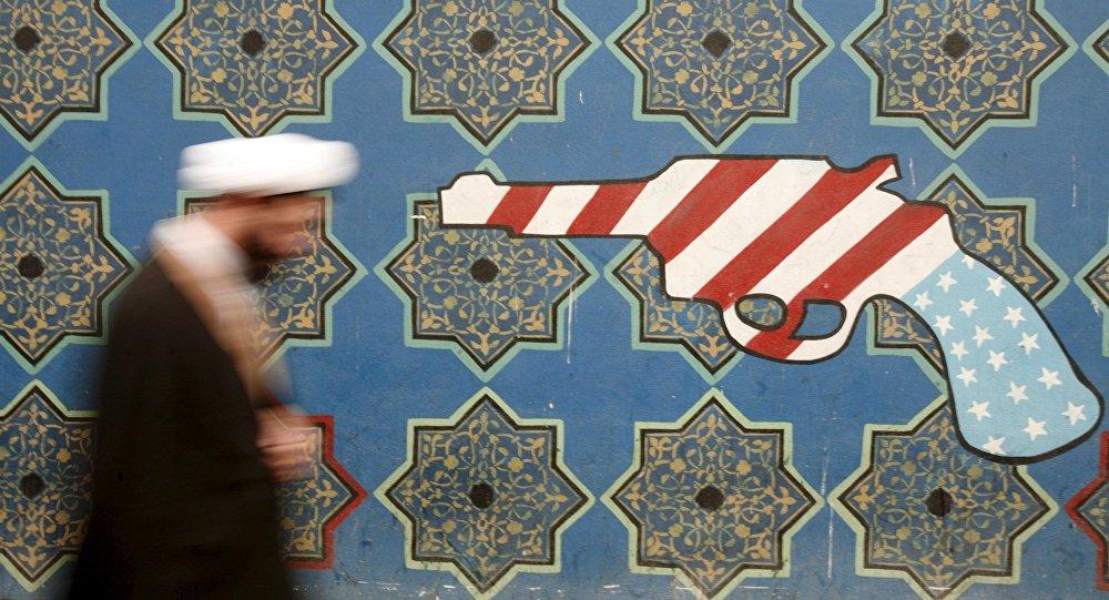 Íránský duchovní prochází kolem malby na zdi bývalého velvyslanectví USA v Teheránu