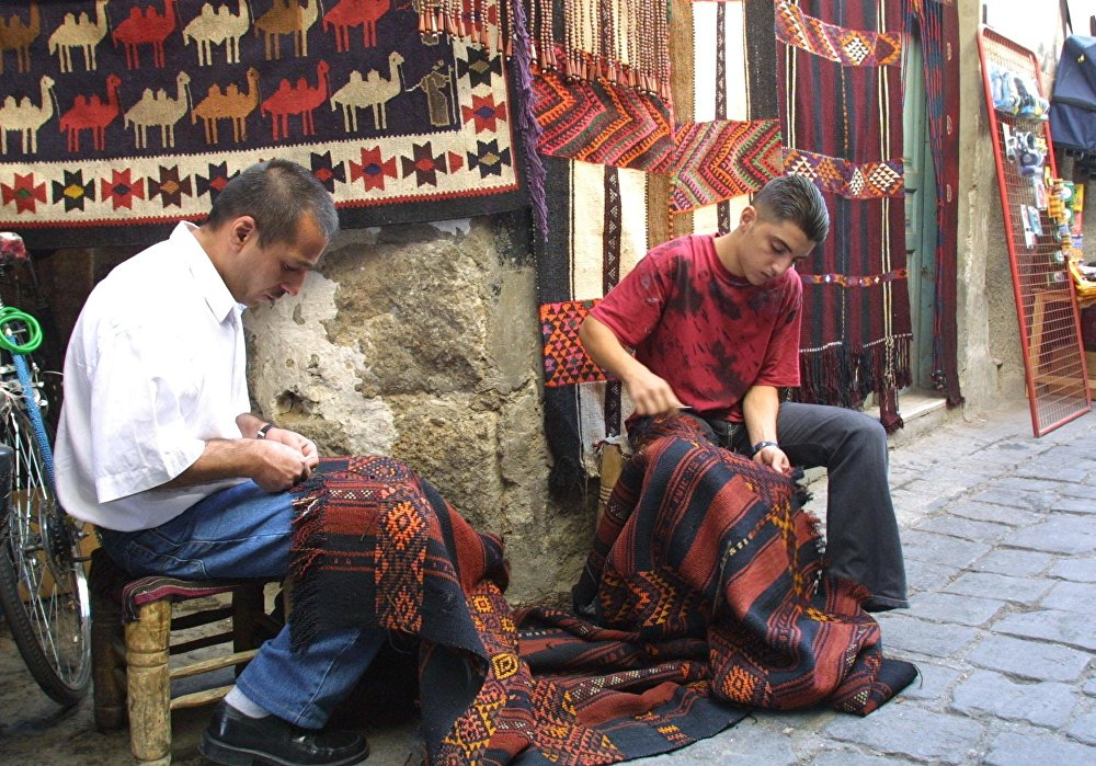 Syřané tkají koberec.