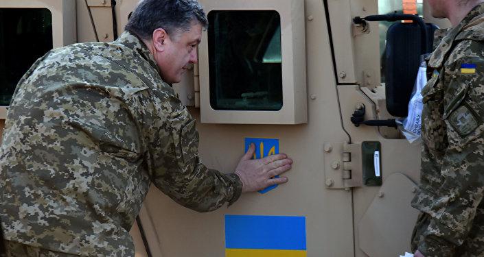 Ukrajinský prezident Petro Porošenko nalepuje ukrajinskou vlajku na Humvee