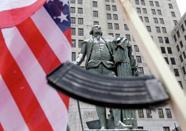Americká vlajka a samopal vlastní výroby vedle sochy George Washingtona v New Yorku