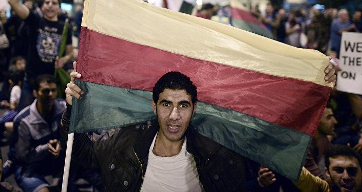 Muž drží vlajku syrské kurdské Strany demokratické unie (PYD)