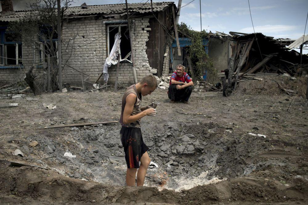 Místní obyvatelé po ostřelování ve vesnici Luganská