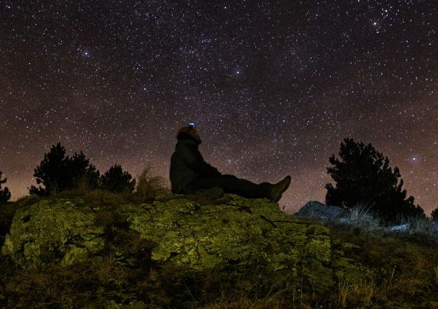 Muž se dívá  na hvězdy