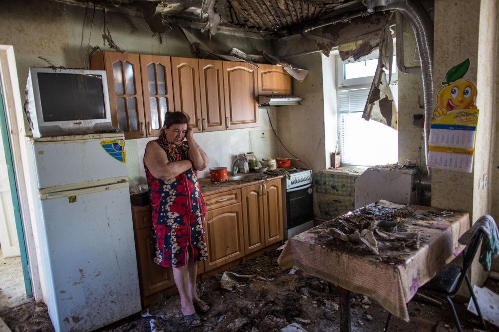 Žena ve svém zničeném domě