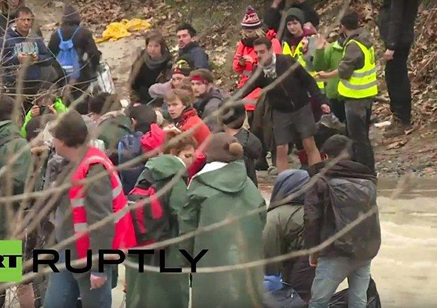 Utečenci se pokoušejí překročit řeku na řecko–makedonské hranici