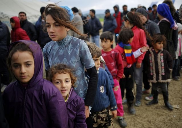 Běženci ve frontě na čaj v stanovém táboru v řecké osadě Idomeni