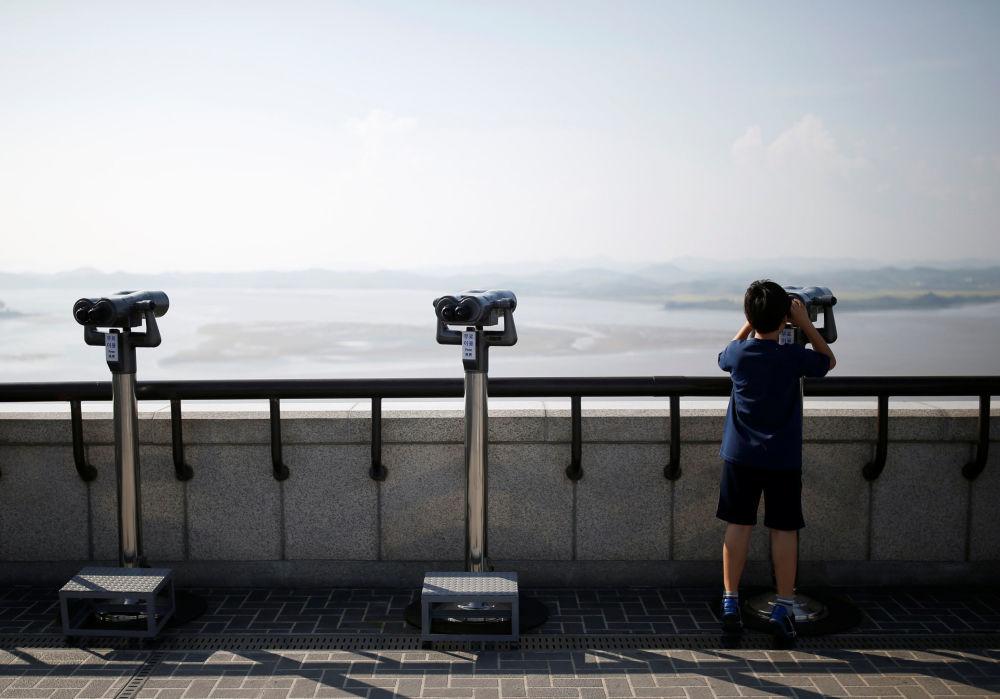 Kluk s dalekohledem vedle demilitarizované zóny mezi Severní a Jižní Koreou