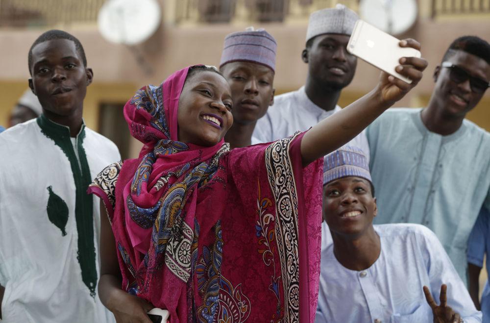 Dívka dělá selfii s přáteli během svátku Kurban-bajram, Nigérie
