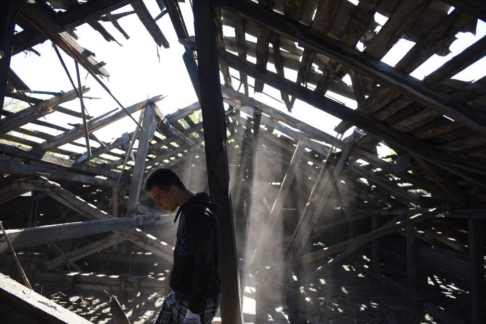 Zničená střepinami střecha střední školy v důsledku nočního ostřelování Makejevky z ukrajinských děl
